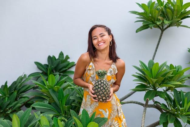 Portret van gelukkige aziatische glimlachende vrouw in gele de greepananas van de de zomerkleding