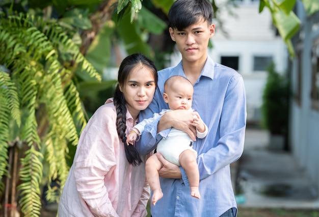 Portret van gelukkige aziatische jonge familie die zich openlucht met glimlach en liefde, moederdag en vaderconcept bevinden.