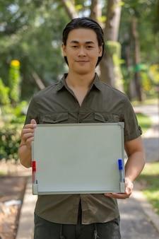 Portret van gelukkige aziatische jonge mens die zich in het park bevindt en leeg uithangbord toont