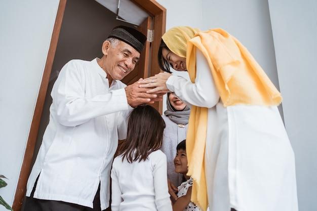 Portret van gelukkige aziatische moslimfamilie die grootouders op ramadan kareem bezoekt. indonesische mensen vieren eid mubarak