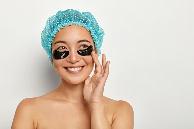 Portret van gelukkige aziatische vrouw met donkere vlekken voor huidverzorging onder de ogen, heeft herstelbehandeling op gezicht, draagt blauwe douchemuts, staat bloot over witte muur, verwijdert rimpels en wallen