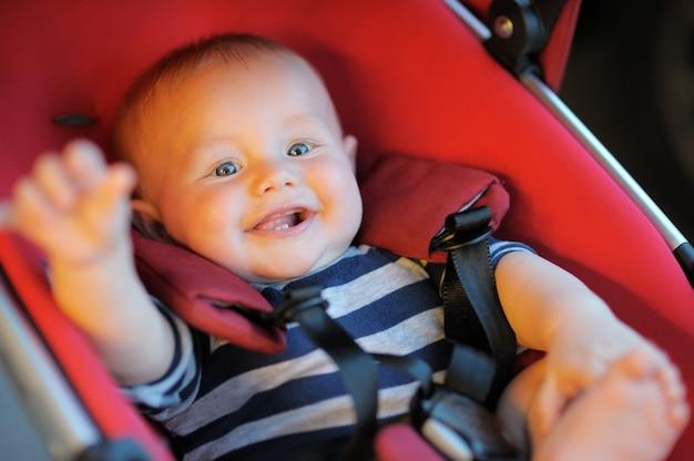 Portret van gelukkige babyjongen in wandelwagen