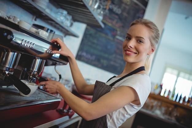 Portret van gelukkige barista die espressomaker met behulp van bij koffie