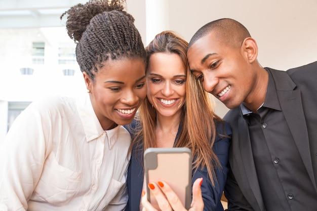 Portret van gelukkige bedrijfscollega's die mobiele telefoon met behulp van