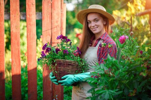 Portret van gelukkige blije bloemisttuinman met bloempot van petunia in openlucht