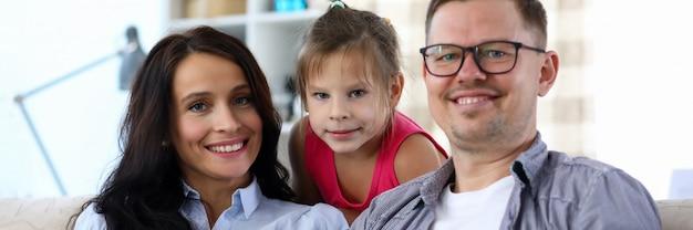 Portret van gelukkige blije familie die moderne tablet samen gebruiken. vrolijke mensen die op bank thuis zitten. mooie moedervader en klein kind die camera met geluk bekijken