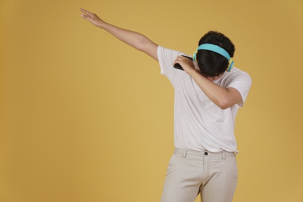 Portret van gelukkige blije vrolijke jonge aziatische man met koptelefoon luisteren naar muziek op smartphone en dansen geïsoleerd