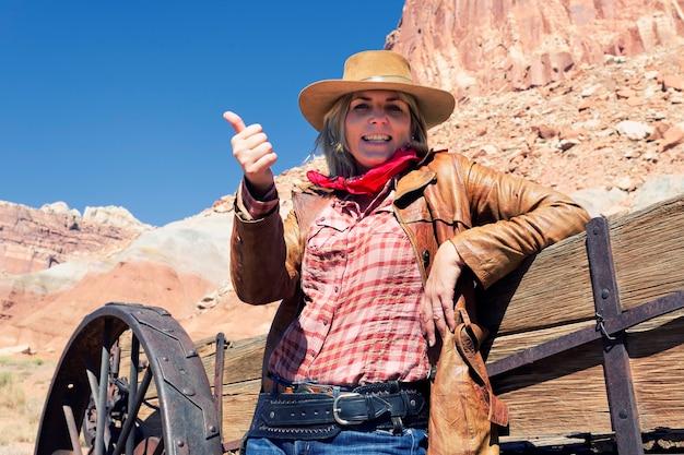 Portret van gelukkige blonde jonge vrouw die een cowboyhoed draagt