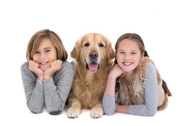 Portret van gelukkige broers en zussen liggend op de vloer met hun hond