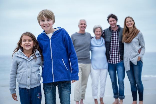 Portret van gelukkige broers en zussen terwijl familie op achtergrond