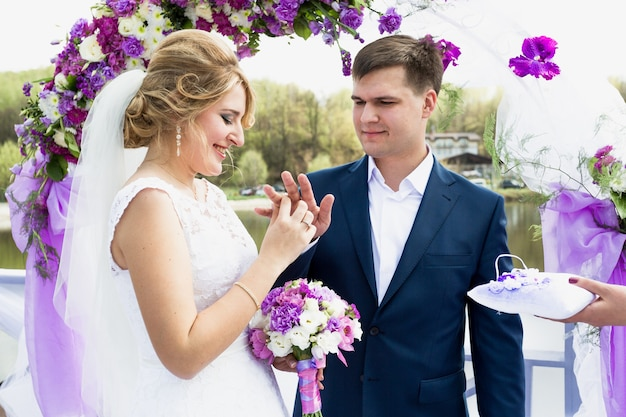 Portret van gelukkige bruid die gouden ring op de hand van de bruidegom zet bij huwelijksceremonie