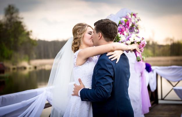 Portret van gelukkige bruid en bruidegom die kussen op zonsondergang bij rivier