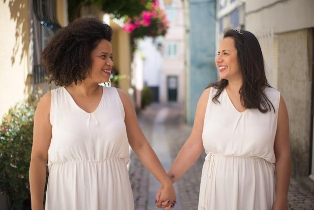 Portret van gelukkige bruiden die door de straat gaan