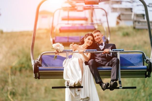 Portret van gelukkige bruidspaar in kabelbaan.