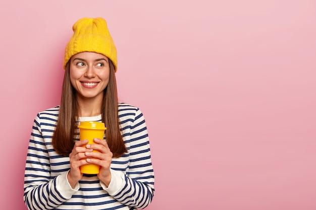 Portret van gelukkige brunette vrouw houdt afhaalkoffie, draagt gele hoed en casual gestreepte trui, kijkt opzij met glimlach, geïsoleerd over roze muur