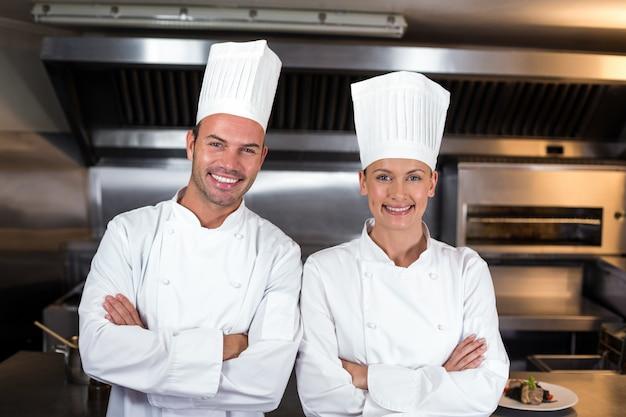 Portret van gelukkige chef-koks die zich in keuken bevinden