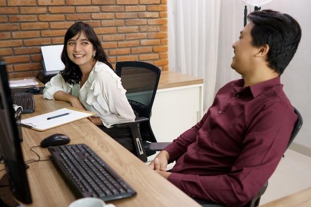 Portret van gelukkige collega's zitten naast elkaar in klein kantoor met gesprek