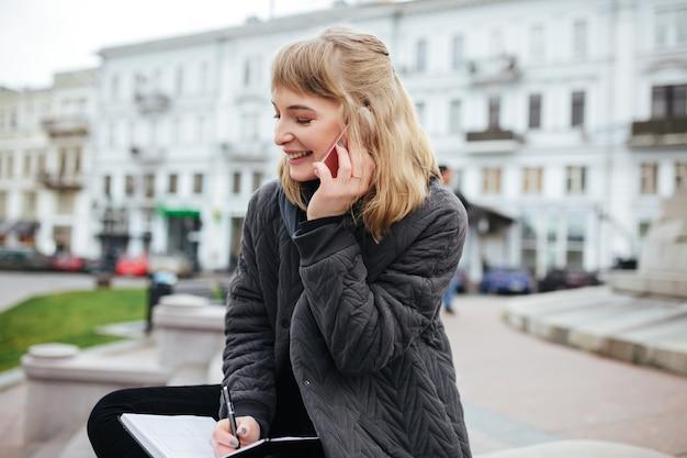 Portret van gelukkige dame met blond haar praten over haar mobiel met laptop in de hand op straat in de stad