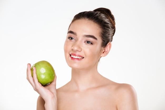 Portret van gelukkige donkerbruine vrouw die groene appel houdt en weg kijkt