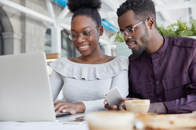Portret van gelukkige donkere studenten ontmoeten elkaar om presentatie of project te laten werken, zitten in cafetaria, informatie op internet zoeken via draagbare laptopcomputer.