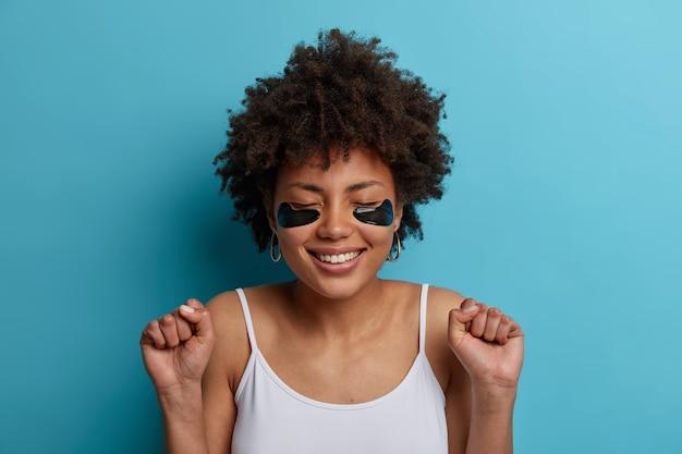 Portret van gelukkige donkere vrouw met schoonheidsgezicht, collageenvlekken onder de ogen voor het verminderen van rimpels, tevreden met nieuw cosmetisch product, balt vuisten van vreugde, lacht breed, heeft een goed humeur
