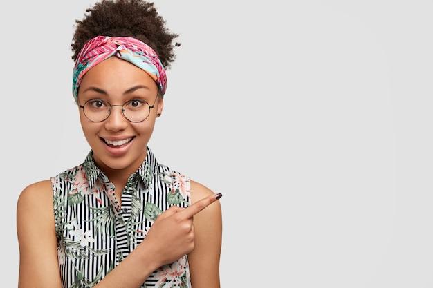 Portret van gelukkige donkere vrouwelijke verkoper, wijst met wijsvinger in de rechterbovenhoek met copyspace