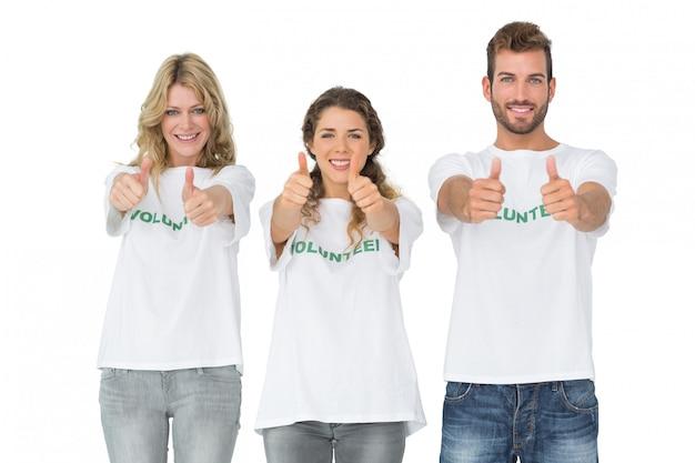 Portret van gelukkige drie vrijwilligers die duimen omhoog gesturing
