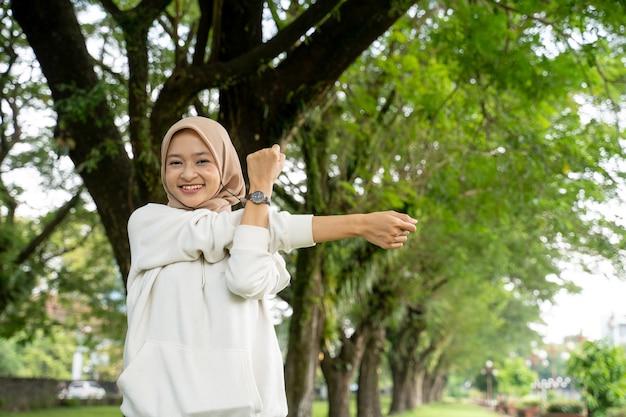 Portret van gelukkige en leuke moslimvrouw die in de ochtend buiten uitoefenen doet