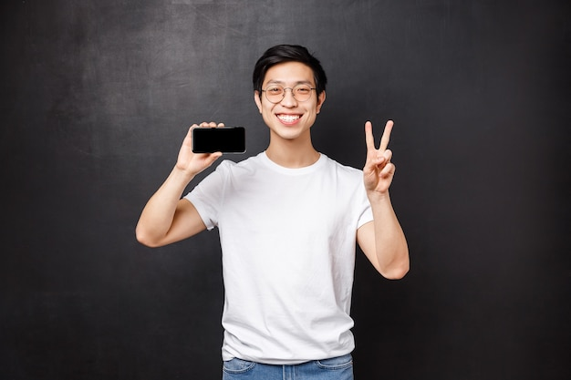 Portret van gelukkige en tevreden jonge aziatische kerel die smartphone houdt en overwinningsteken doet