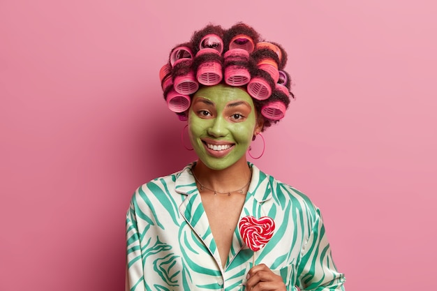 Portret van gelukkige etnische vrouw draagt groene gezichtsmasker, glimlacht toothily, houdt lolly, maakt krullend kapsel met rollen, draagt casual binnenlandse kleding,