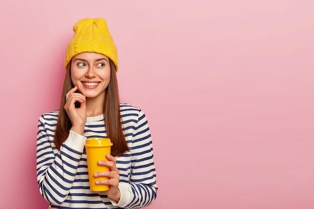 Portret van gelukkige europese vrouw met blije uitdrukking, lacht aangenaam en kijkt opzij, houdt afhaal koffie, geniet van warme drank tijdens wandeling, draagt stijlvolle hoed en casual trui, modellen binnen