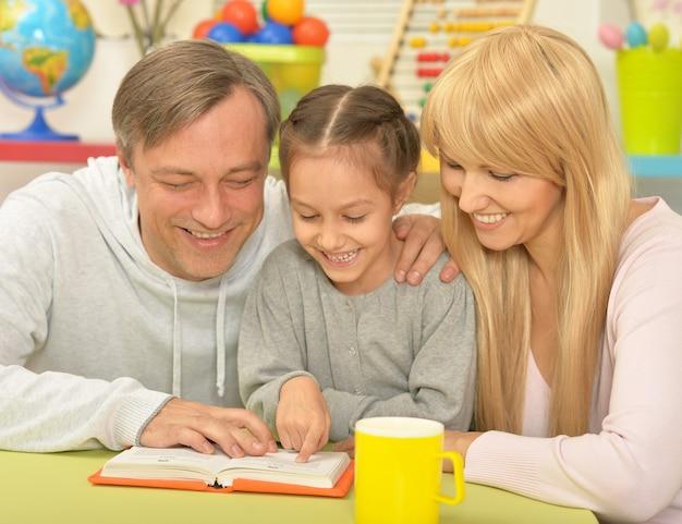 Portret van gelukkige familie die het boek thuis leest