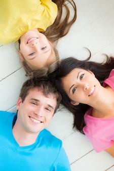 Portret van gelukkige familie die thuis op de vloer ligt
