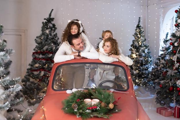 Portret van gelukkige familie in rode auto dichtbij kerstbomen.