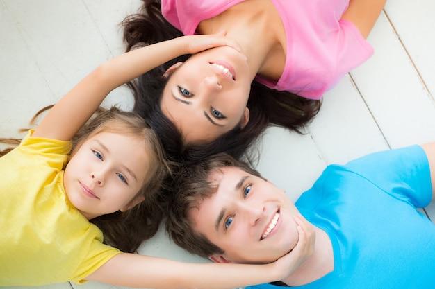 Portret van gelukkige familie liggend op de vloer. gelukkig gezin plezier thuis fun