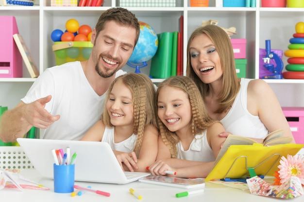 Portret van gelukkige familie met laptop thuis