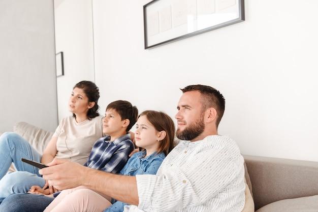 Portret van gelukkige familie met twee kinderen rusten in de huiskamer, en samen op de bank zitten terwijl u tv kijkt
