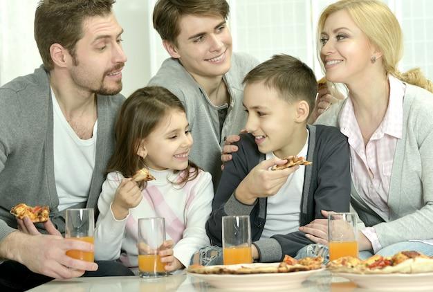 Portret van gelukkige familie thuis met pizza