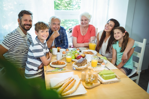 Portret van gelukkige familiezitting bij ontbijtlijst