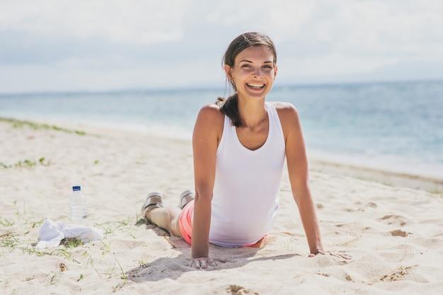 Portret van gelukkige gezonde vrouw doet push-up op het strand