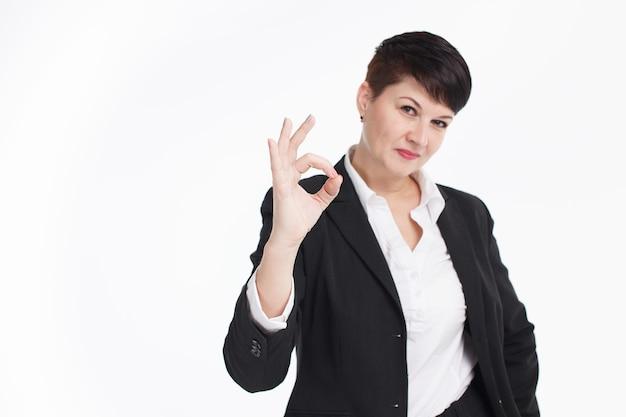 Portret van gelukkige glimlachende bedrijfsvrouw met ok gebaar, op witte achtergrond