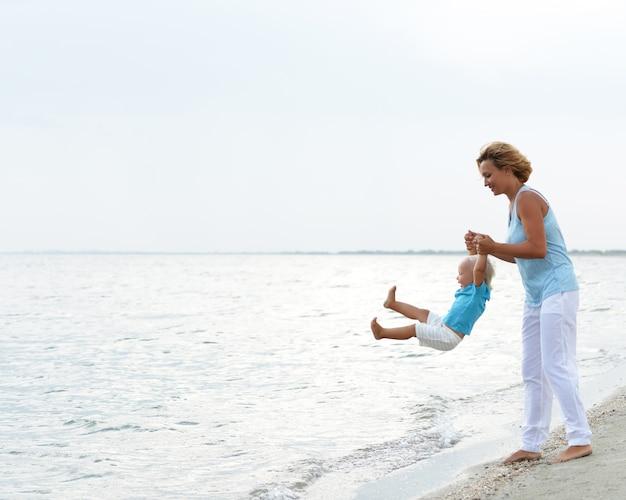 Portret van gelukkige glimlachende jonge moeder met klein kind dat op het strand speelt.