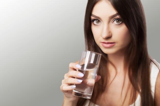 Portret van gelukkige glimlachende jonge vrouw met glas zoet water