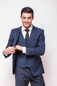 Portret van gelukkige glimlachende jonge zakenman in blauw kostuum dat op witte muur wordt geïsoleerd