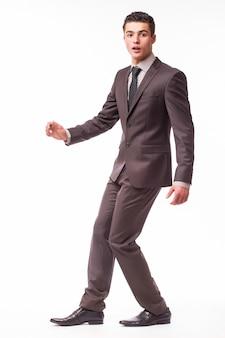 Portret van gelukkige glimlachende jonge zakenman in bruin kostuum dat op witte muur wordt geïsoleerd
