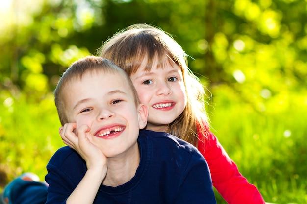 Portret van gelukkige glimlachende kleine kinderenjongen en meisje op de zonnige weide van het de zomergras.