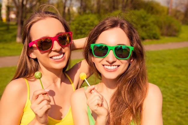Portret van gelukkige glimlachende meisjes die in brillen lollys houden