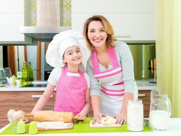 Portret van gelukkige glimlachende moeder en dochter die taarten samen maken bij de keuken.