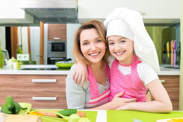 Portret van gelukkige glimlachende moeder en dochter in roze schort bij de keuken.