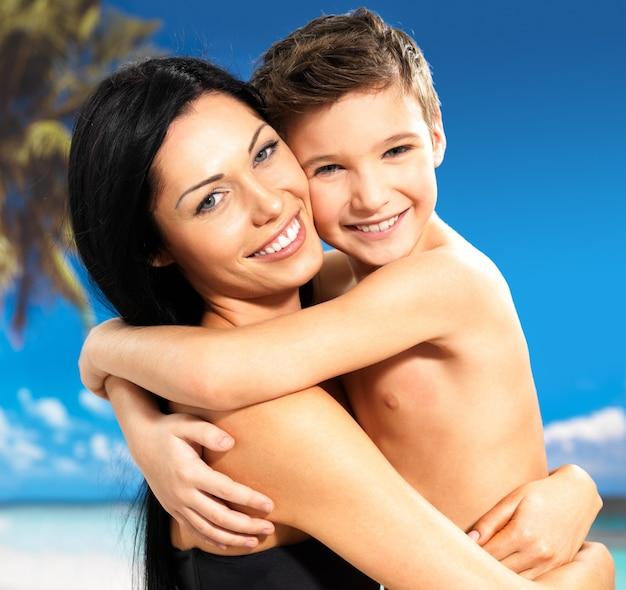 Portret van gelukkige glimlachende moeder koestert zoon 8 jaar oud bij tropisch strand